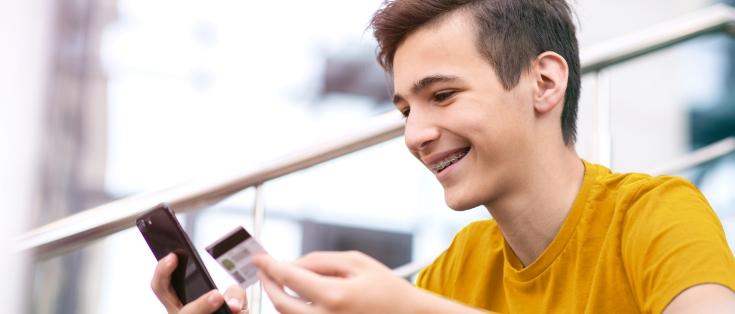Młody chłopak trzymający karę debetową ismartfona